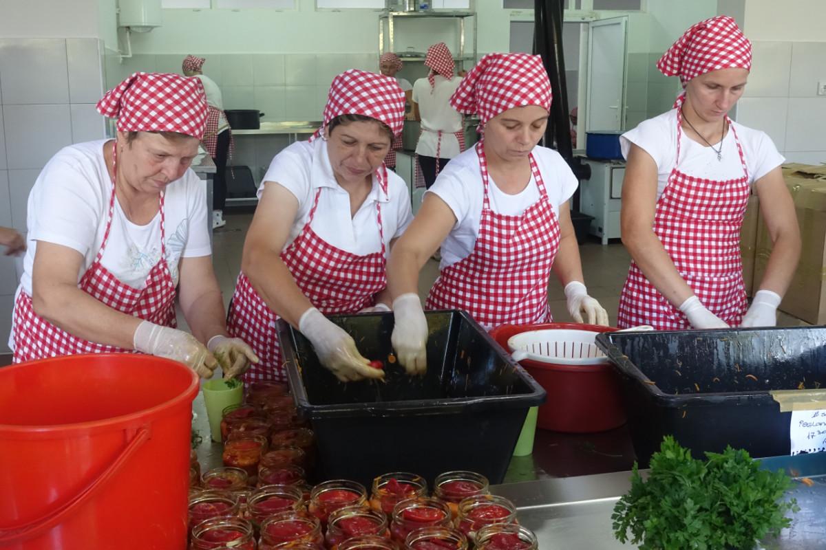 Frauen beim Einlegen von roten Paprika